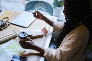 Thoughtful experienced tourist thinking on writing interesting speech in notebook for meeting international student sitting in coffee shop with tasty coffee and using modern technology