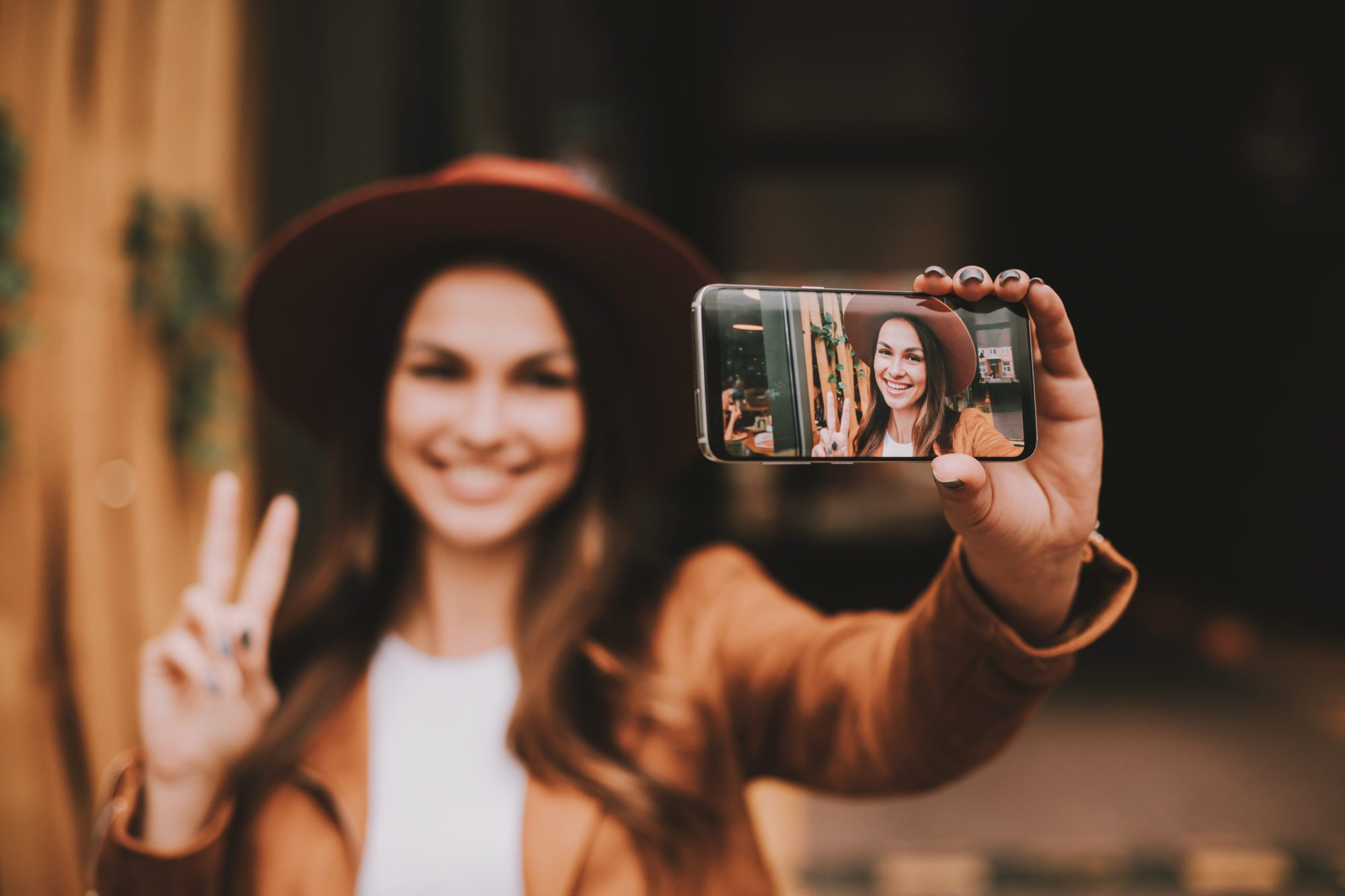 Woman taking selfie with phone holding up peace sign